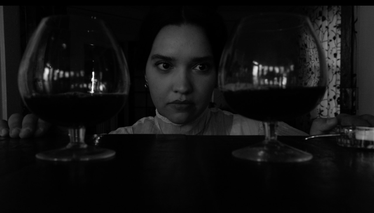 Black and white, a woman's face framed by wine glasses on either side.