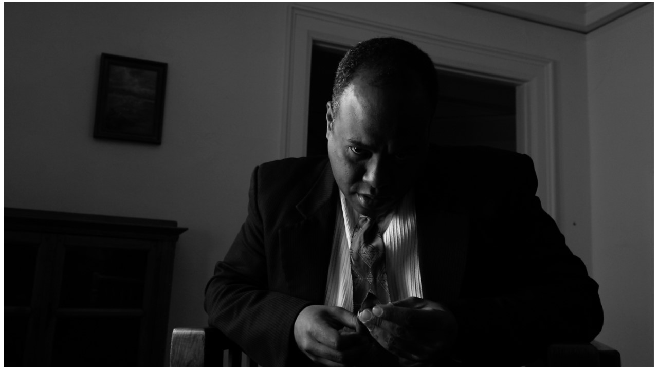Black and white, a man in a suit contemplates a dagger held in his hand