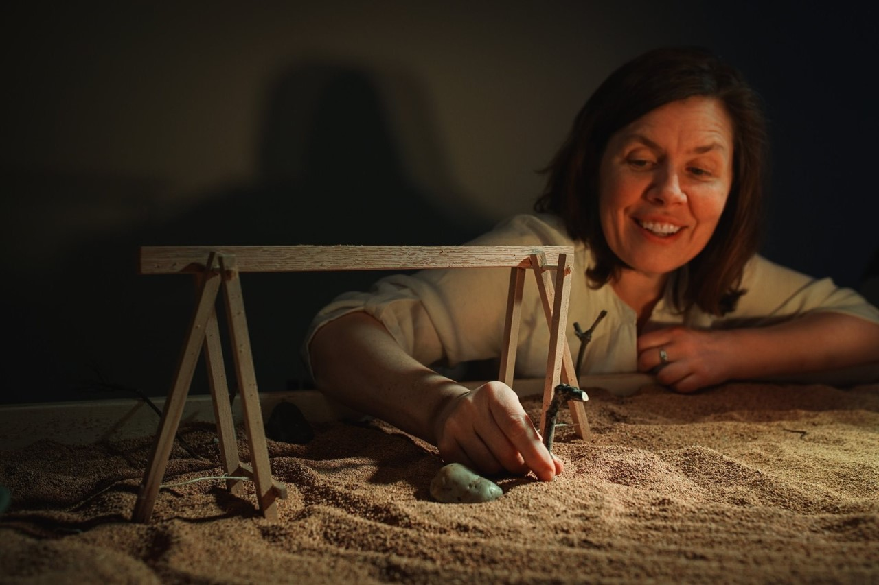 A woman builds a small wooden structure atop sand.