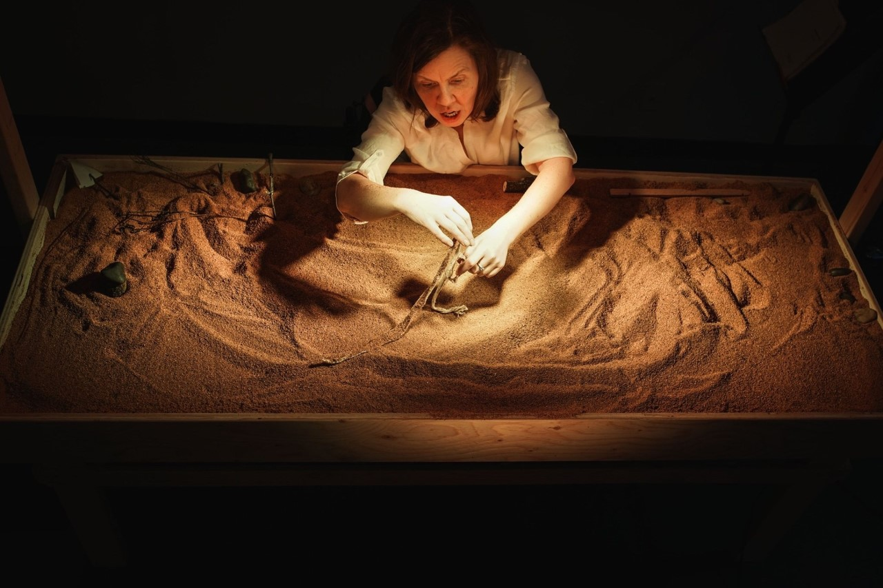 A woman seated at a table, drawing in sand